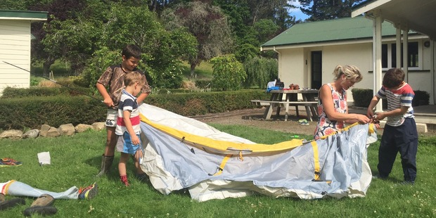 Lizzie Hay and her sons, McGregor, 3, Sam, 6, and Ben, 8, pitch a tent after their house was damaged in last night's aftershock. Photo / Kurt Bayer