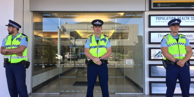 Hamilton police stand guard outside the Hamilton regional office of Department of Corrections this morning. Photo / Belinda Feek
