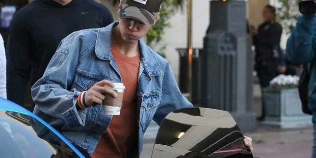 Justin Bieber drinks a coffee whilst leaving The Grove in his blue Ferrari in West Hollywood, California. Photo / Splash News