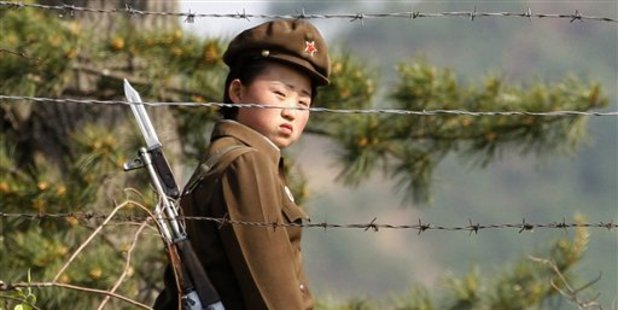 In this file photo, a female North Korean soldier looks out from behind a barbed-wire fence around a prison camp. Photo / AP