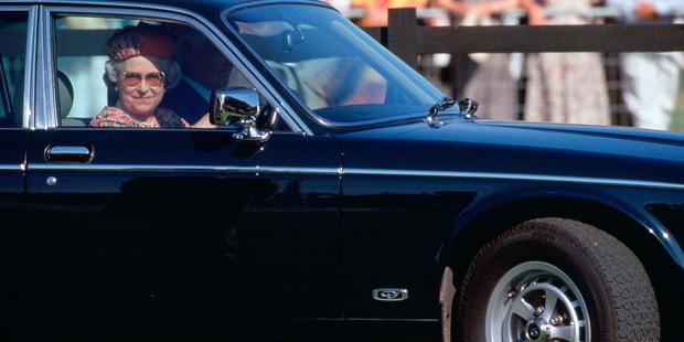 Queen Elizabeth II driving her Daimler Jaguar car. Photo / Getty Images