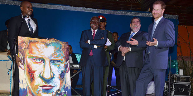 Prince Harry receives a painting of himself from local artist Calvert Jones. Photo / Getty