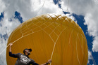 Site manager Stephen Bradshaw clings to the Orbserver's balloon, which takes $100,000 of helium to fill. Photo / NZME