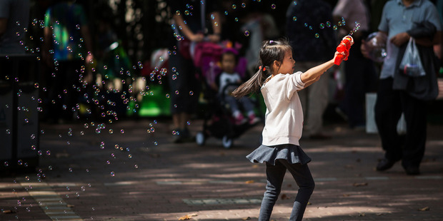 A young girl blows bubbles with a bubble gun at the Lu Xun Park in Shanghai, China. Photo / Bloomberg