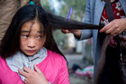 In a small, rural village 14-year-old Qingwen Liu gets her ponytail cut off to sell for money.