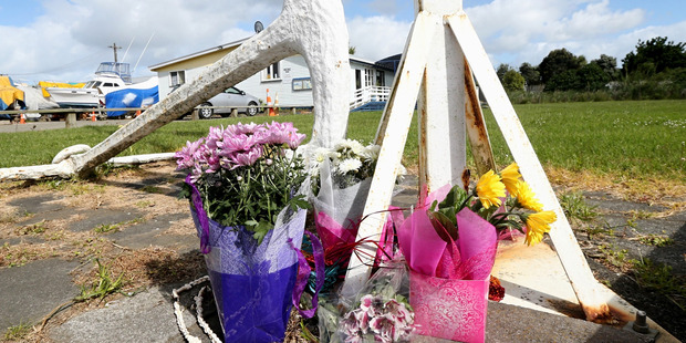 Flowers at the base of the flag pole at the Kaipara Cruising ans Sportfishing Club in Helensville to honour the drowned fishermen. Photo / Jason Oxenham