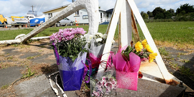 Flowers at the base of the flag pole at the Kaipara Cruising and Sportfishing Club in Helensville to honour the drowned fishermen. PHOTO/Jason Oxenham