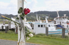 Flowers on the flag pole at the Kaipara Cruising and Sportfishing Club in Helensville to honour the drowned fishermen. Photo / Jason Oxenham
