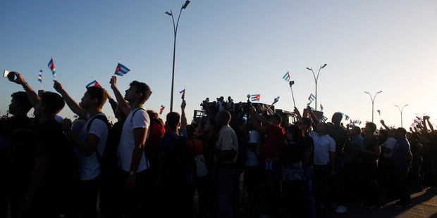 People wave Cuban national flags as they watch the motorcade transporting the remains of Cuban leader Fidel Castro drive past. Photo / AP