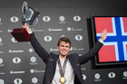 Magnus Carlsen, of Norway, smiles as he holds up his championship trophy during the award ceremony for the World Chess Championship. Photo / AP