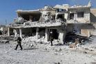 Civil Defense workers walk past damaged buildings after airstrikes hit in Abian Saman town, in rural western Aleppo. Photo / AP