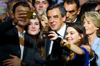 Francois Fillon, a candidate in Sunday's primary runoff to select a conservative candidate for the French presidential election, poses for a selfie with supporters during a rally in Paris. Photo / AP