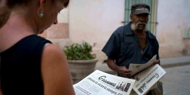 A tourist buys a copy of the Granma newspaper announcing the death of Cuban leader Fidel Castro. Photo / AP