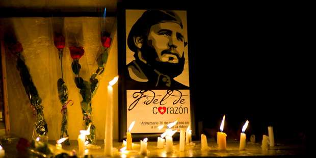An image of the late Cuban leader Fidel Castro, surrounded by candles and roses, leans against a wall of the university where Castro studied law as a young man. Photo / AP