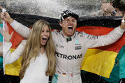 Mercedes driver Nico Rosberg of Germany celebrates with his wife Vivian Sibold holding a German flag in the team garage after winning the F1 2016 Championship. Photo / AP.