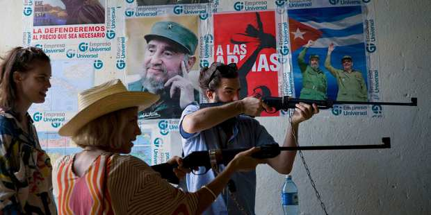 Loading Tourists shoot compressed air rifles next to posters of Cuba'a late leader Fidel Castro at a recreational center in Havana, Cuba. Photo / AP