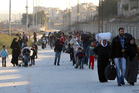 People flee rebel-held eastern Aleppo into the Sheikh Maqsoud area. Photo / AP