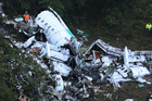 Rescue workers stand at the wreckage site of a chartered airplane tha was carrying the Brazilian first division soccer club Chapecoense team. Photo / AP