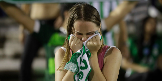 A fan of Brazil's soccer team Chapecoense mourns during a gathering inside Arena Conda stadium in Chapeco, Brazil. Photo / AP