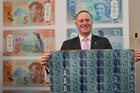 Prime Minister John Key with the new $10 bank notes. Photo / Mark Mitchell