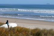 A surfer heads out at Papamoa Beach. Photo/ John Borren