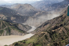 Dust created by a strong aftershock hangs above the Clarence River which was blocked, causing a huge dam, north of Kaikoura. Photo / Mark Mitchell