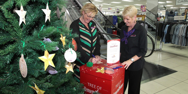 Sam Robson (left) and Trish Knigh, staff at Farmers, Hastings, signing a card to go on a Tree of Remembrance supporting Cranford Hospice. Photo / Duncan Brown