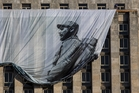 Men hang a giant banner with a picture of Cuba's late leader Fidel Castro. Photo / AP
