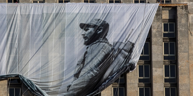 Loading Men hang a giant banner with a picture of Cuba's late leader Fidel Castro. Photo / AP