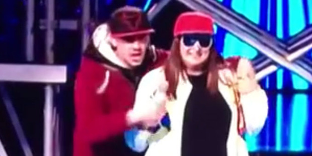 Loading Honey G has her microphone taken by a stage invader during the latest episode of The X Factor UK. Photo/YouTube