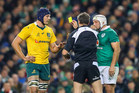 Australia's Dean Mumm is shown a yellow card by referee Jerome Garces. Photo INPHO/James Crombie