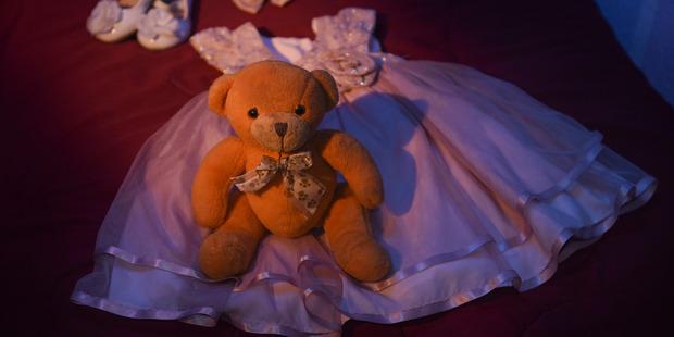 A toy bear, dress, shoes and bow sit at the home of Saira and Farhan Khan for the daughter of Syed Rizwan Farook and Tashfeen Malik. Photo /Washington Post, Jahi Chikwendiu