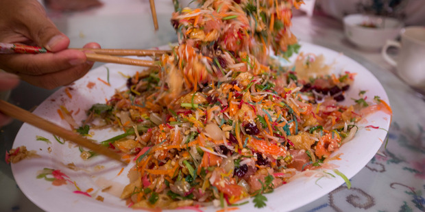 Prosperity toss consists of raw fish mixed with shredded vegetables and a variety of sauces and condiments. Photo / Dean Purcell