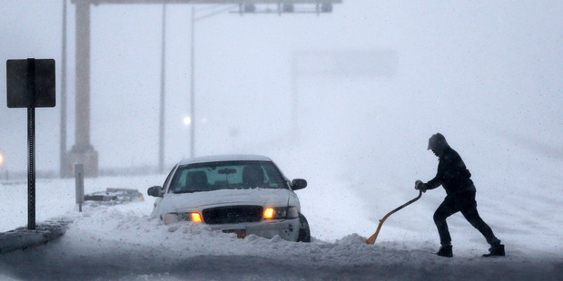 A motorist shovels snow to free up a vehicle on the New Jersey Turnpike. Photo / AP