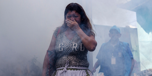 A woman covers her mouth while city workers fumigate insecticide in San Salvador, El Salvador. Photo / AP