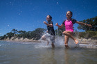 Billy Brown, 9, left, and Ellie Brown, 12, (brother and sister) crash into the water to beat the hot weather at Narrow Neck Beach. Photo / Jason Oxenham