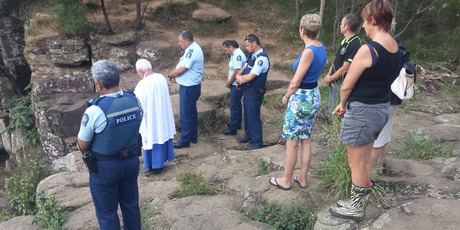 BLESSING: The scene of Tuesday's drowning at Charlie's Rock is blessed by Minister Sid Kingi while police officers and local residents show their respects. PHOTO / SUPPLIED