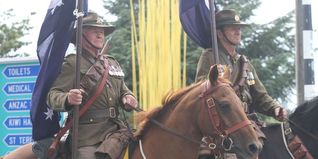 Mike Donaldson, left, and Terry King, from the New Zealand Mounted Rifles Charitable Trust, march their horses on to Fitzherbert St in Featherston. PHOTO/ANDREW BONALLACK