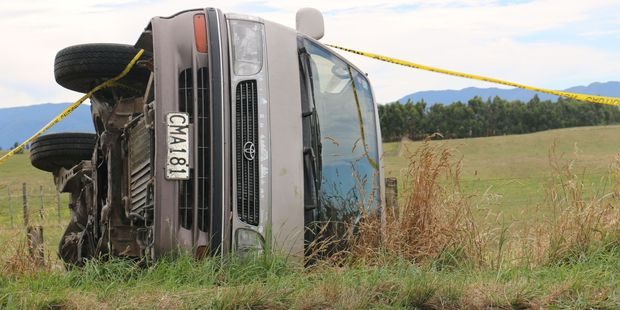 A Toyota Hiace van on its side at Dyerville, south of Martinborough, after the driver lost control. He was uninjured in the crash. PHOTO/NZME