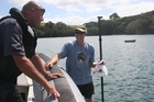 Police Constable Marco van den Broek chats to camper Phillip Mayall, who paddled out from a DoC campground in the Bay of Islands for some fishing information. Photo / DOC