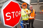 Bryan (left) and Peter Brooks test out the new remote-controlled stop/go sign. Photo / Kellie Blizard