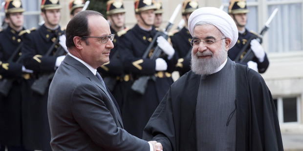 Francois Hollande, France's president welcomes Hassan Rouhani, Iran's president, in the courtyard of Elysee Palace in Paris, France. Photo / Bloomberg