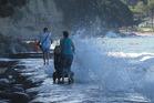 A mother pushing a pram at Mairangi Bay is battered by waves. Photo / Eliane Souza Araujo