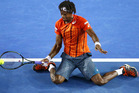 Gael Monfils drops to his knees to return a shot to Milos Raonic. photo / Getty