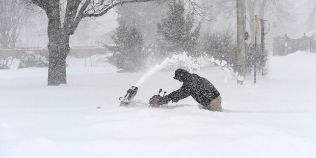 David Colwell steers a snow blower through thigh-deep snow to clear the sidewalk in his neighbourhood. Photo / Washington Post