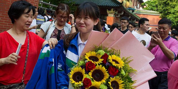 A student walks with flowers from her relatives after completing the Gaokao in Guangzhou, China. Photo / Getty Images