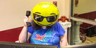 A woman speaks on the phone in her office while wearing pretending her face is actually a smiley-face balloon.