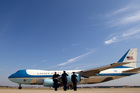 Military personnel salute as Air Force One. Photo / AP