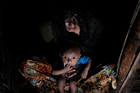 Mohsena Begum, a Rohingya who escaped to Bangladesh from Myanmar, holds her child and sits at the entrance of a room of an unregistered refugee camp in Teknaf. Photo / AP