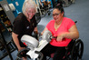 Irene Frost helps stroke sufferer Mary-Anne Stone on the new, $10,000 'MOTOmed' machine at Kensington FItness. Photo / Michael Cunningham